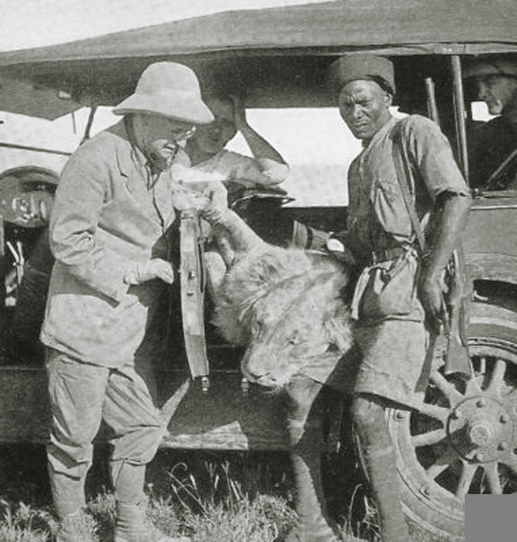 British East Africa hunter and askari with dead lion in the safari vehicle  1920.jpg