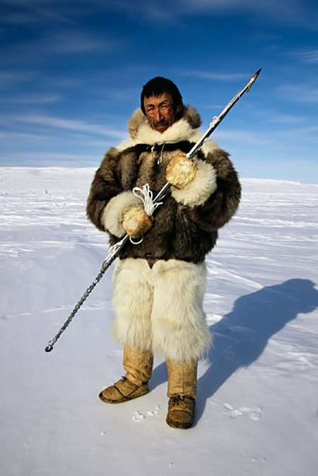Native Inuit seal hunter dressed in polar bear, wolf and seal skins holding a harpoon, Nunavut a.jpg